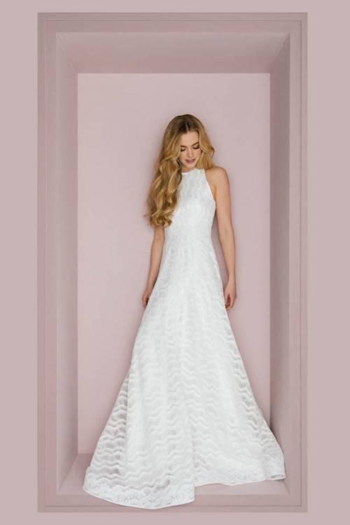 Beige Hochzeitskleid auf Kleiderbügel an der Wand