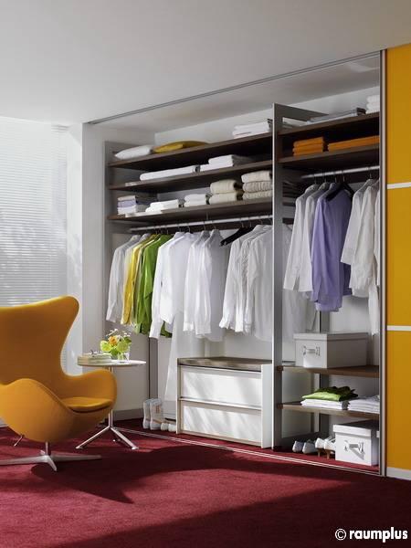 Modernes Schlafzimmer Detail mit einem hölzernen Schlitten Bett, Einbauschrank mit satiniertem Glas Türen, und versenkten Akzentbeleuchtung