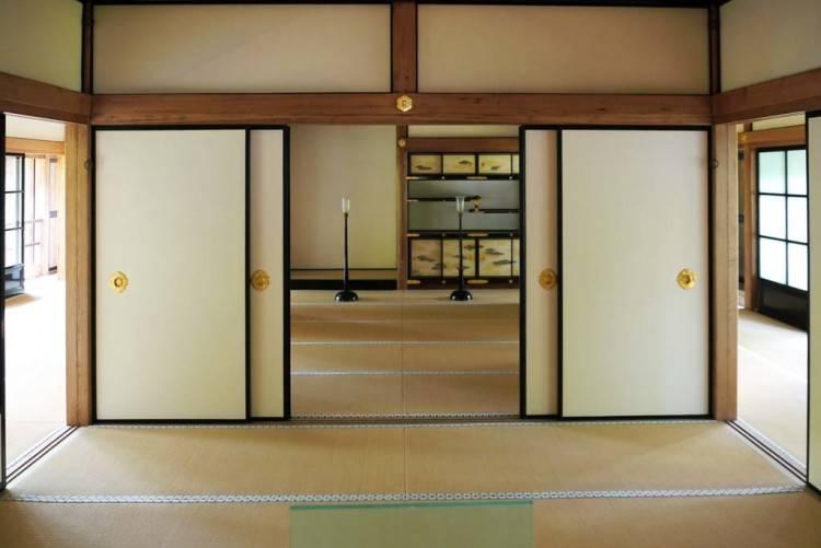 Einfache leichte Schlafzimmer im japanischen Stil mit großem Bett,  gepolsterte Wand, Teppich, drei Bonsaisbäume stehen auf einem Wandregal —  Foto von